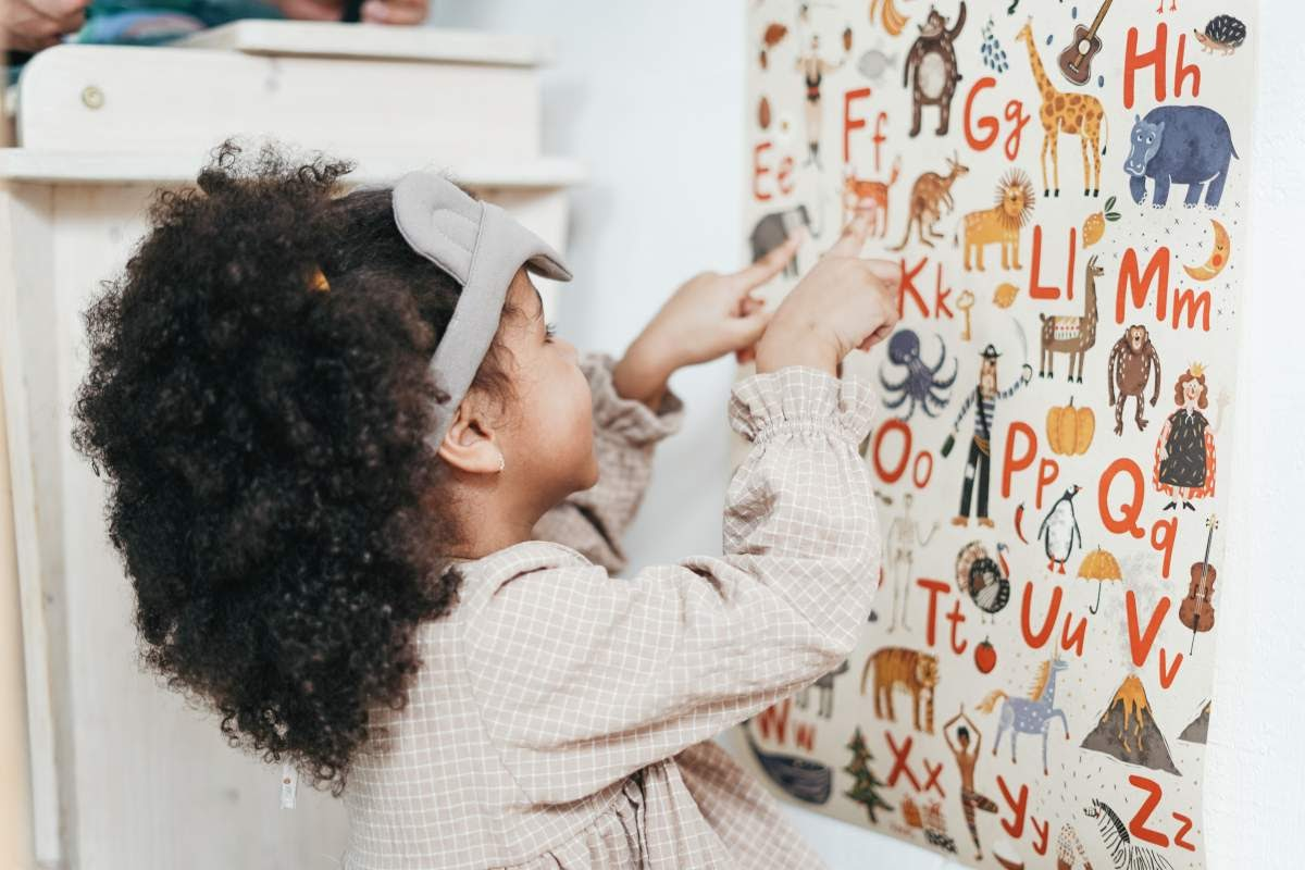Young child pointing to drawings on a pa
