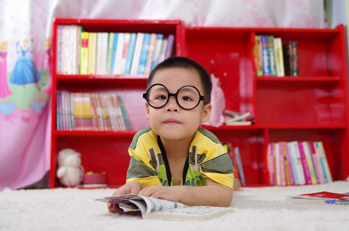 Young boy lying down flipping through a book and wearing big round glasses.