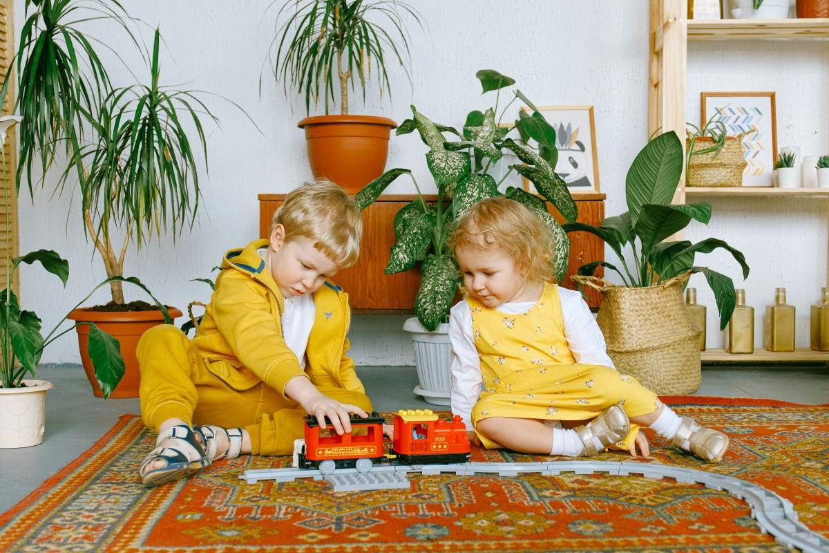Two children both wearing yellow playing with a trainset