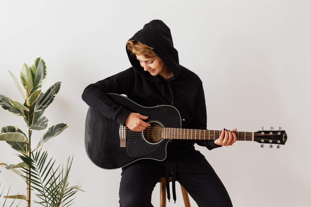 A person dressed in all black playing the guitar next to a plant.