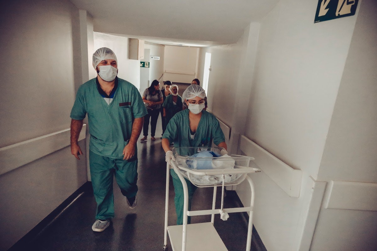 Doctor and nurse bringing premature infant to the NICU