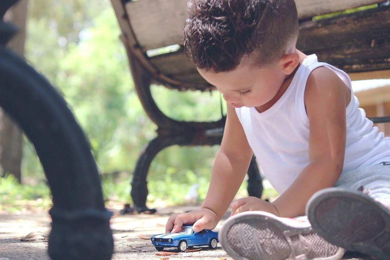 A young boy sits on the ground of a park and plays with his toy car.
