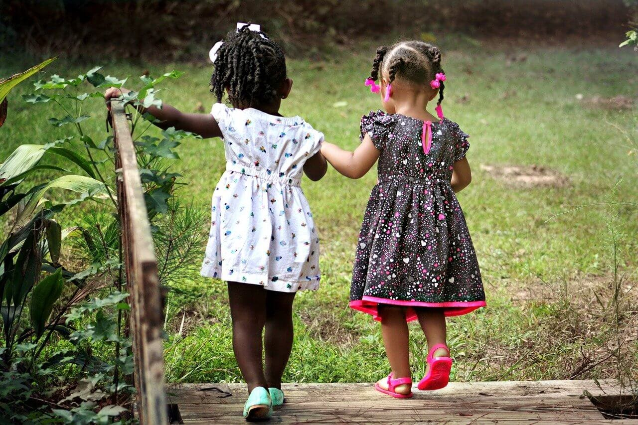Two young girls holding hands as they  explore a grassy field.