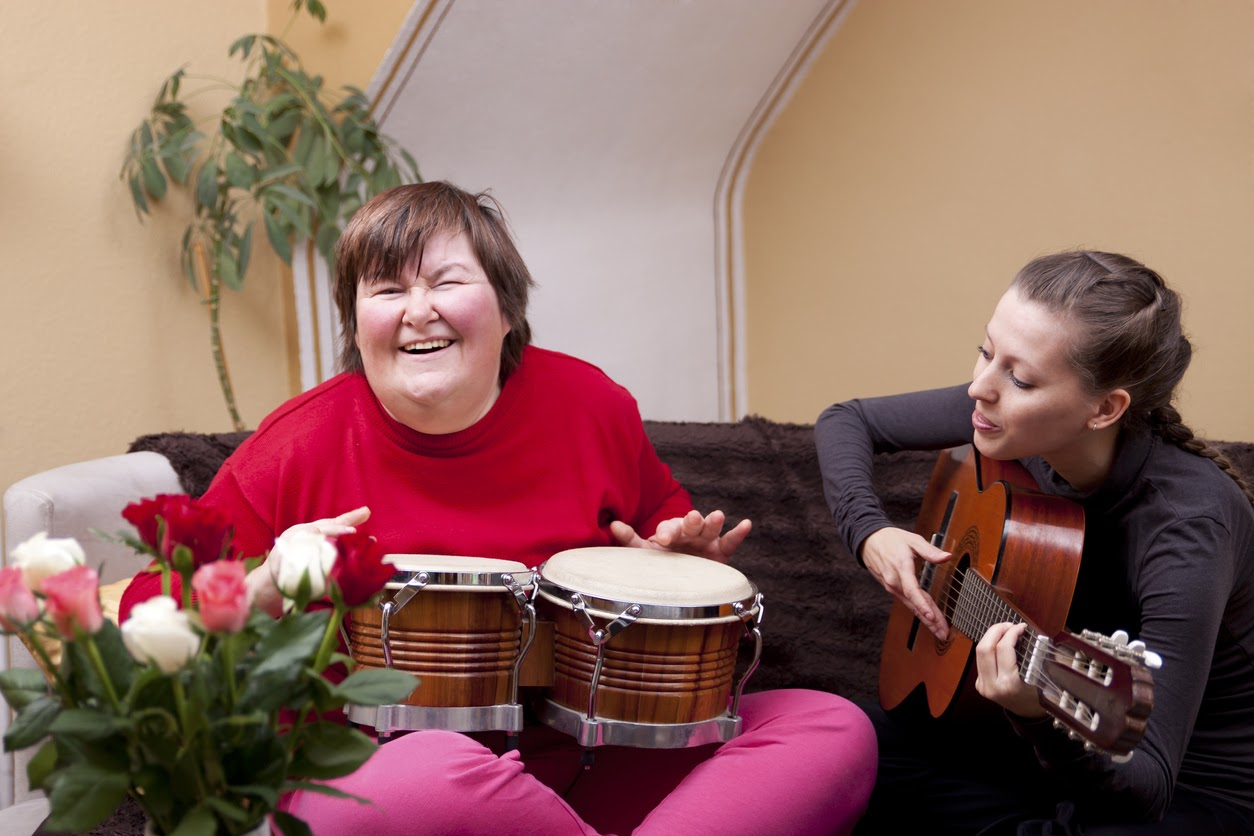 Woman laughing and playing the drums while in resource-oriented music therapy
