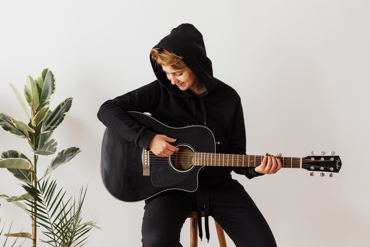 Woman in black sweatshirt participating in resource-oriented music therapy
