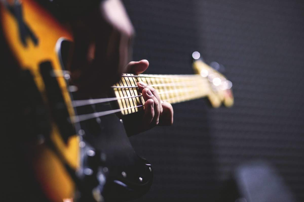 Close up photo of hands playing an electric bass guitar