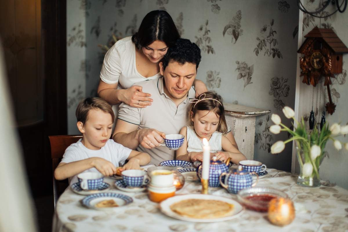 Parents and two children sitting at a table drinking tea