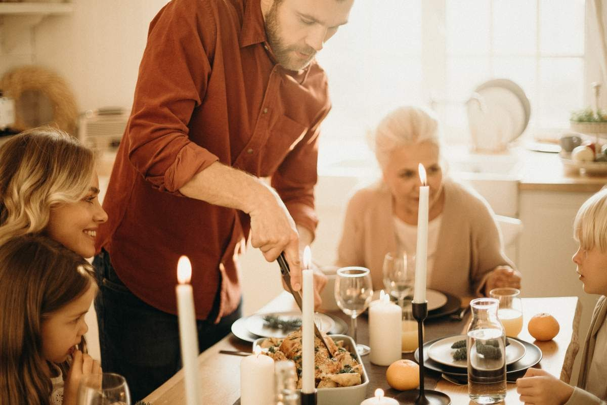man cutting into a piece of meat at a candlelit dinner table with his family