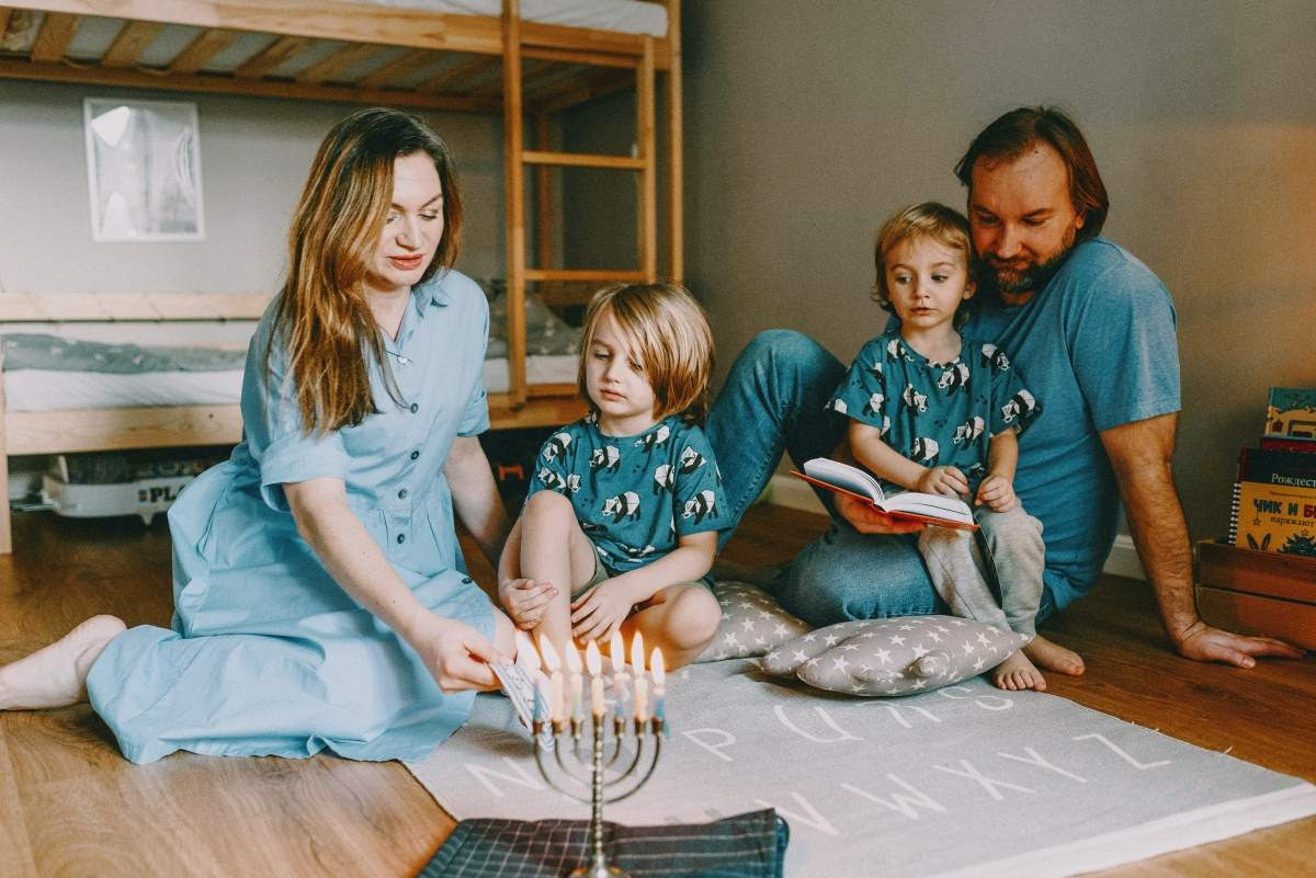 Parents and two children sitting in a kids room in front of a lit menorah