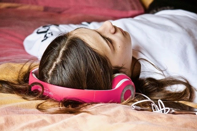 A woman laying down wearing bright pink headphones listening to music