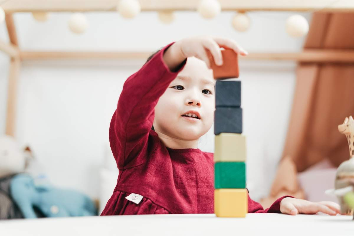Kid in a red dress playing with colorful building blocks