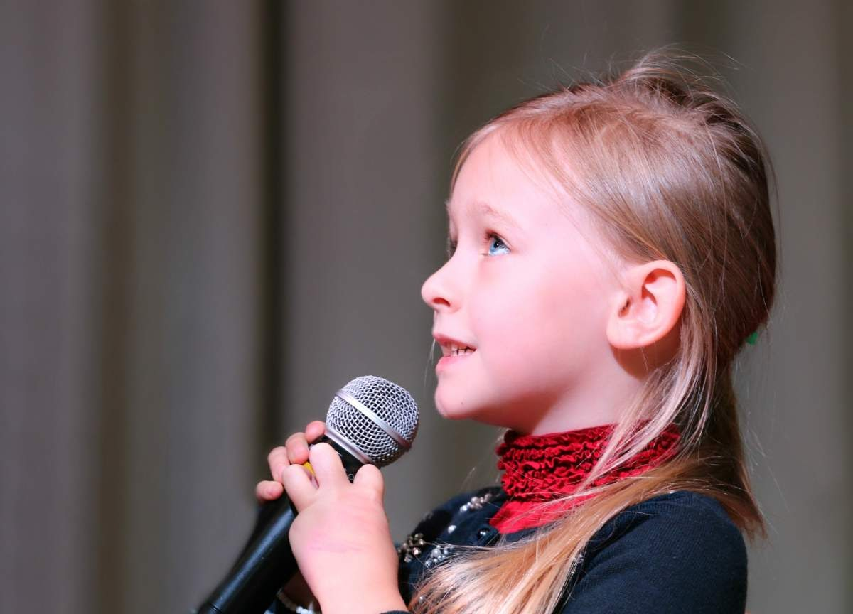 Child wearing a red scarf holding a microphone