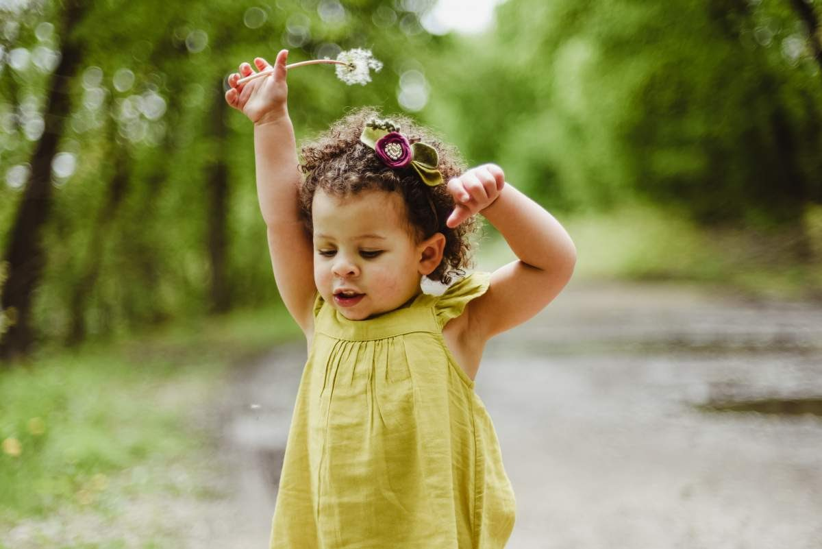 child in a yellow dress holding a dandelion