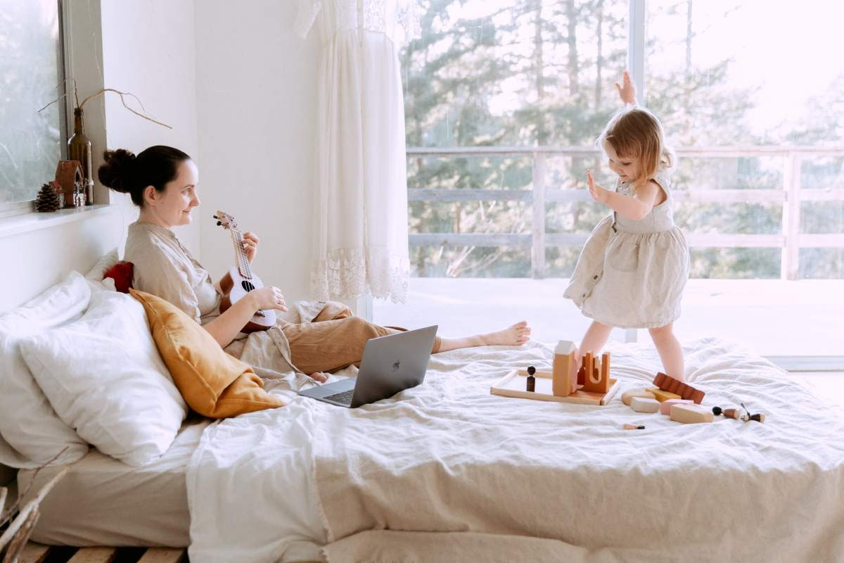 Woman playing the Ukulele in bed and a child playing around on the bed too