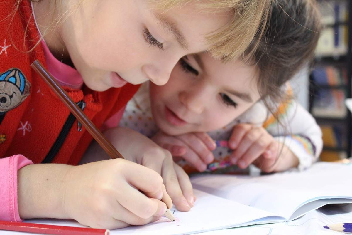 One child writing on a piece of paper while another kid watches