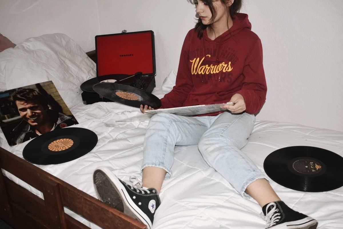 Girl in her bed looking through vinyl records.