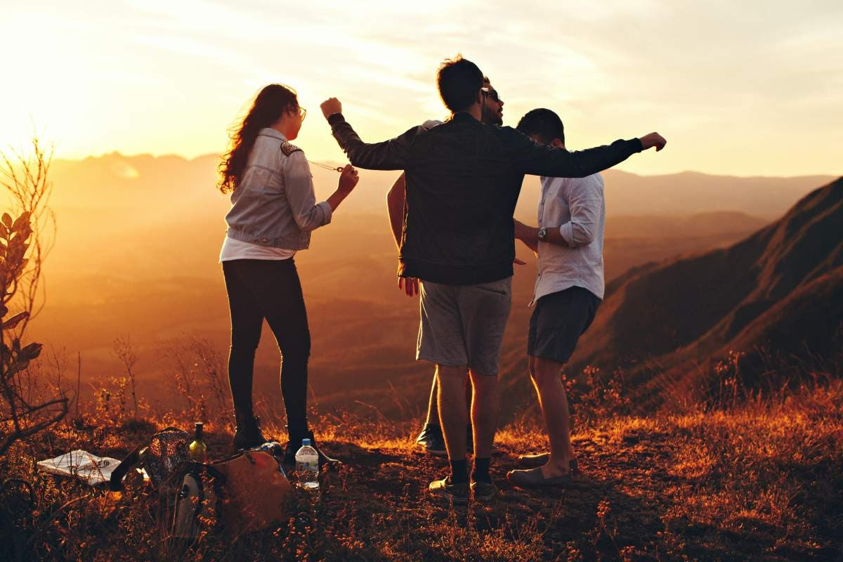 A group of four friends dancing on a hillside at sunset