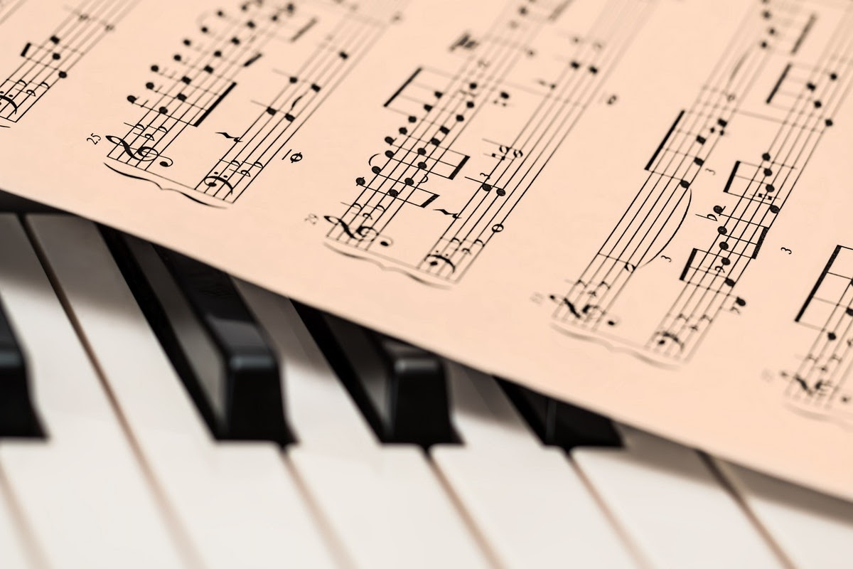 A piece of sheet music rests over piano keys