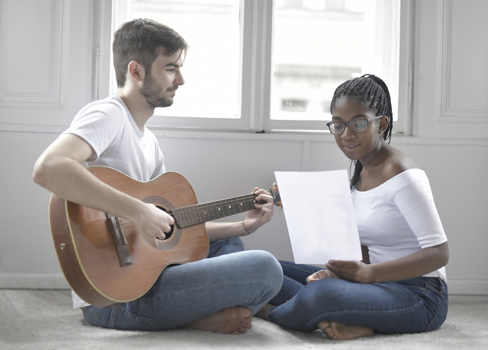Music therapist playing guitar and client singing and utilizing verbal interventions.
