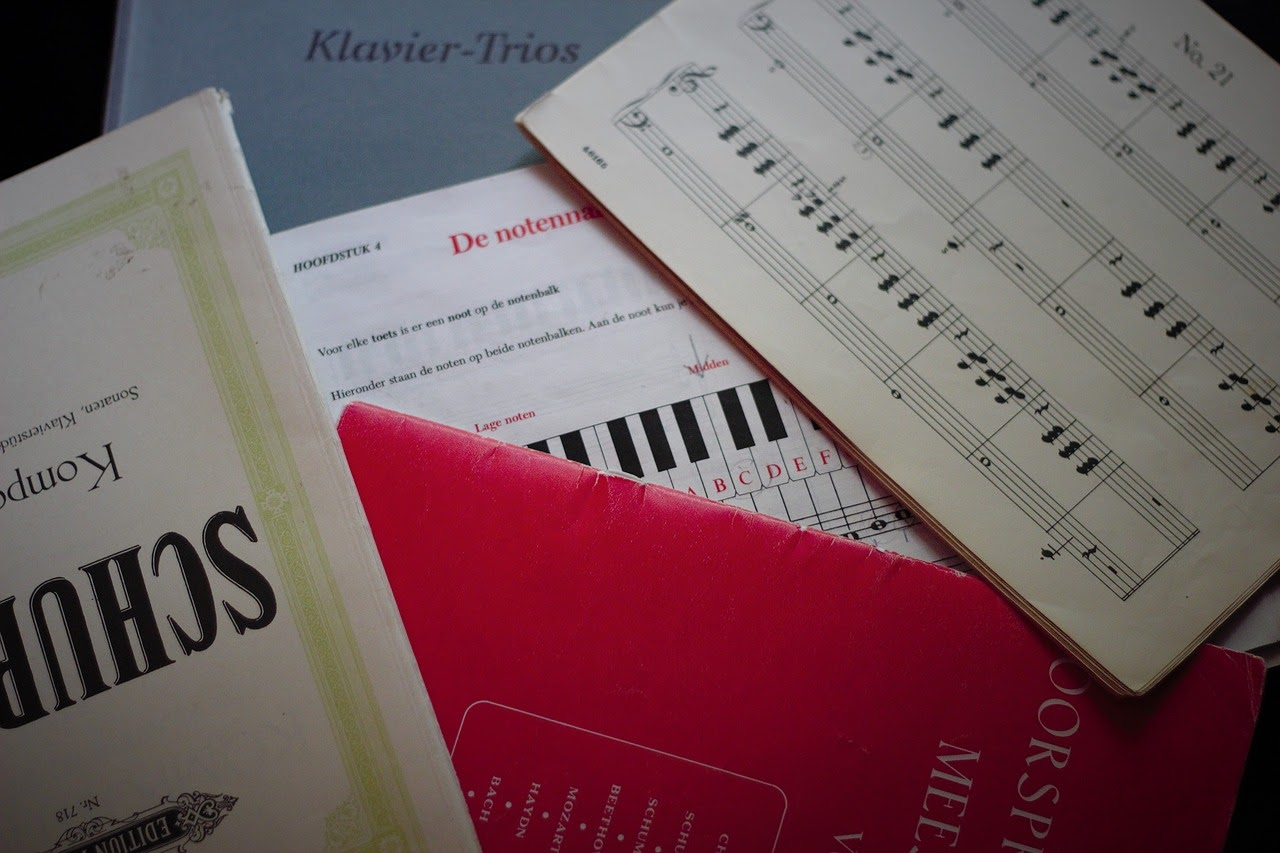 a pile of sheet music and music books