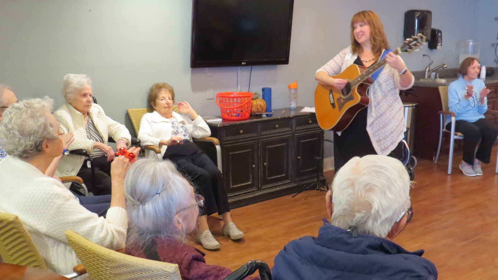 Woman plays guitar for Alzheimer's patients.