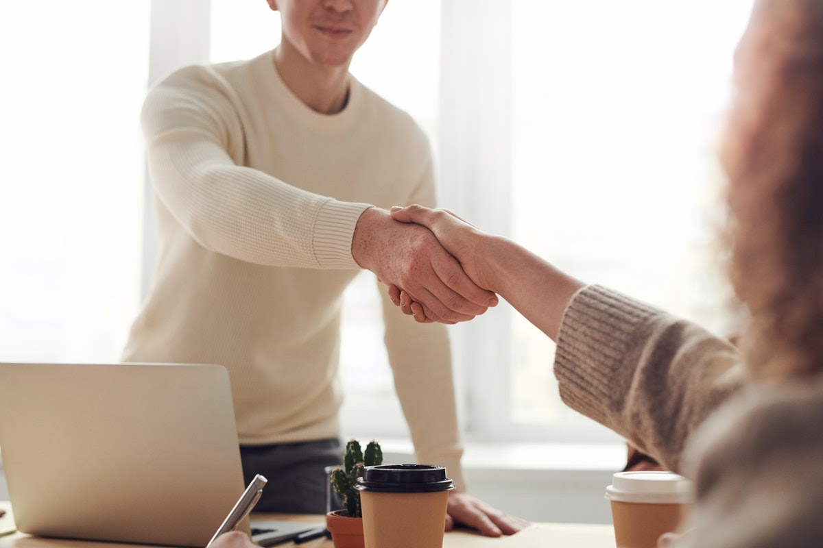 two people sitting on opposite sides of a desk shaking hands