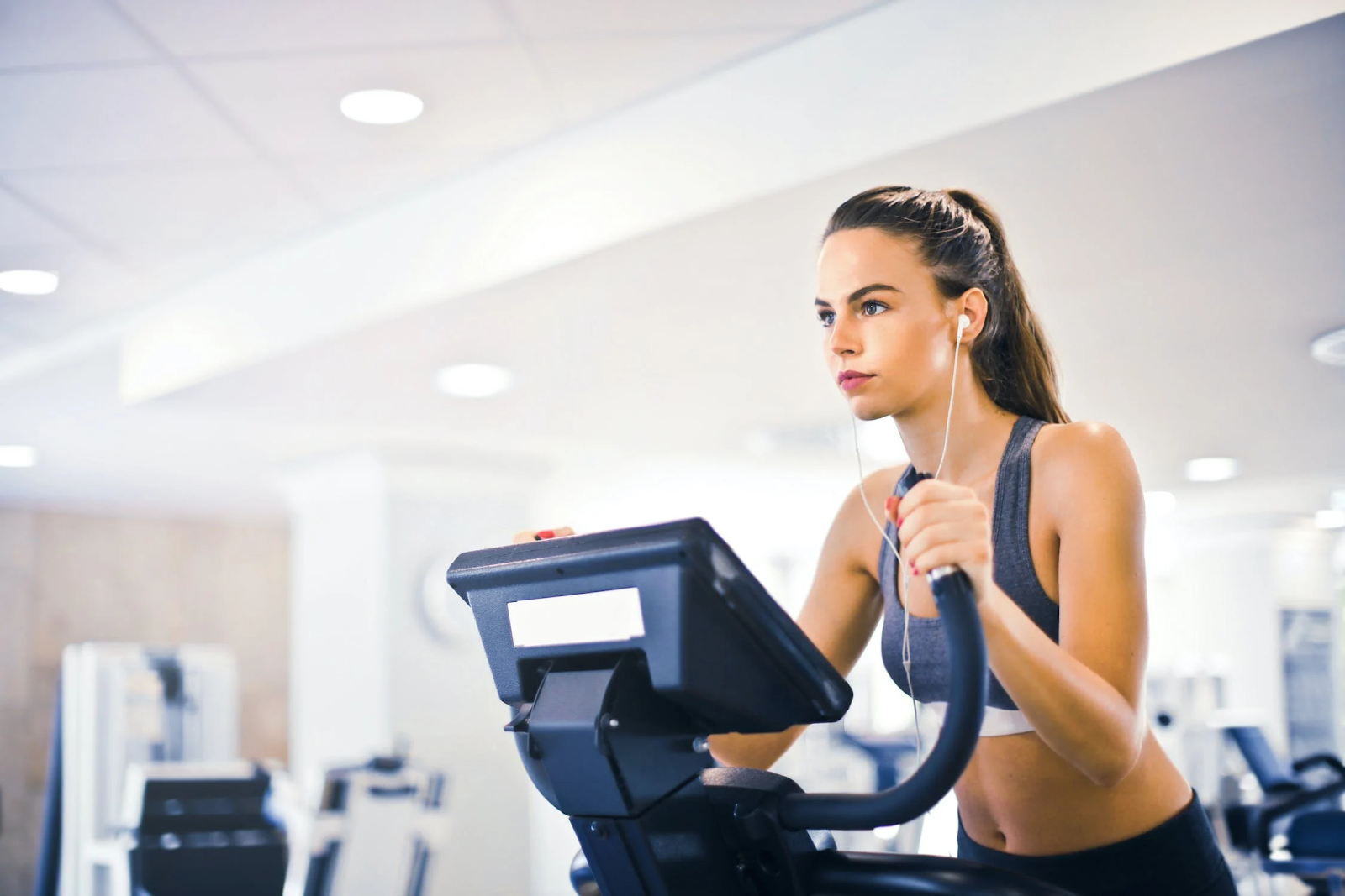 Woman listening to music while she works out on the elliptical.