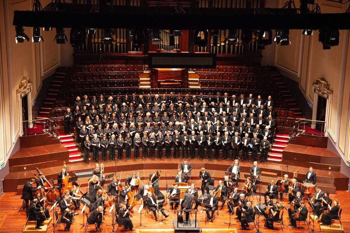 an orchestra and chorus performing on stage