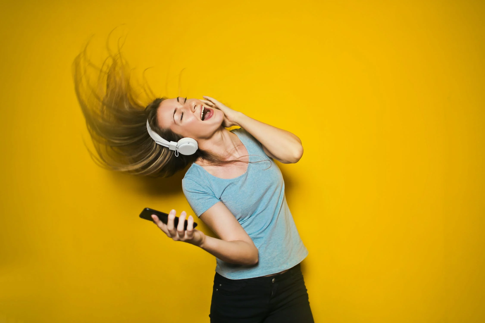 Woman listens to upbeat music to improve her mental health.