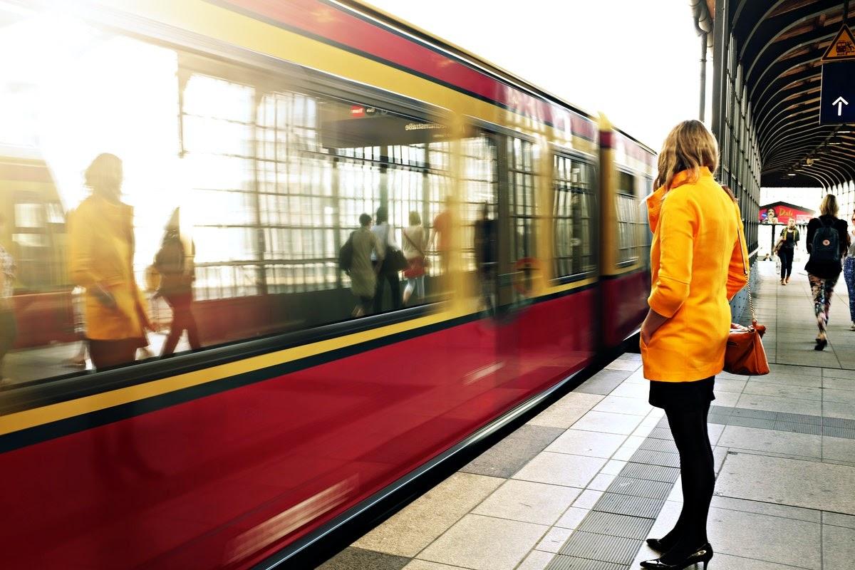 a woman waiting to board a train