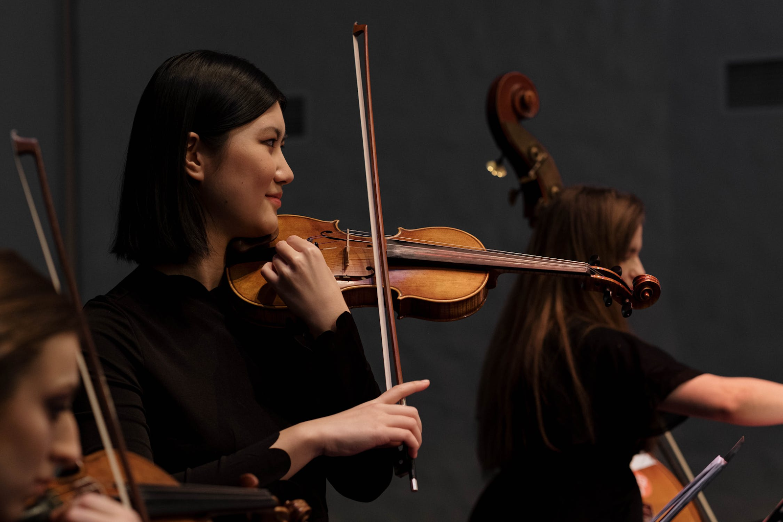 Woman engages with classical music by playing violin.