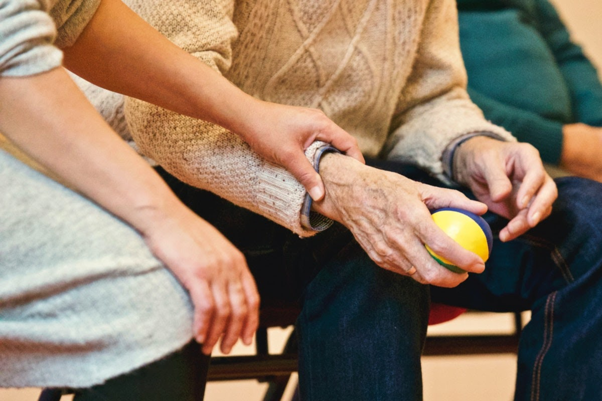 an older adult engaging in a therapy exercise with a ball