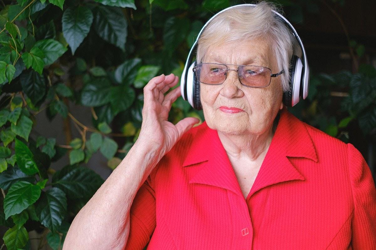 an elderly woman listening to music on headphones