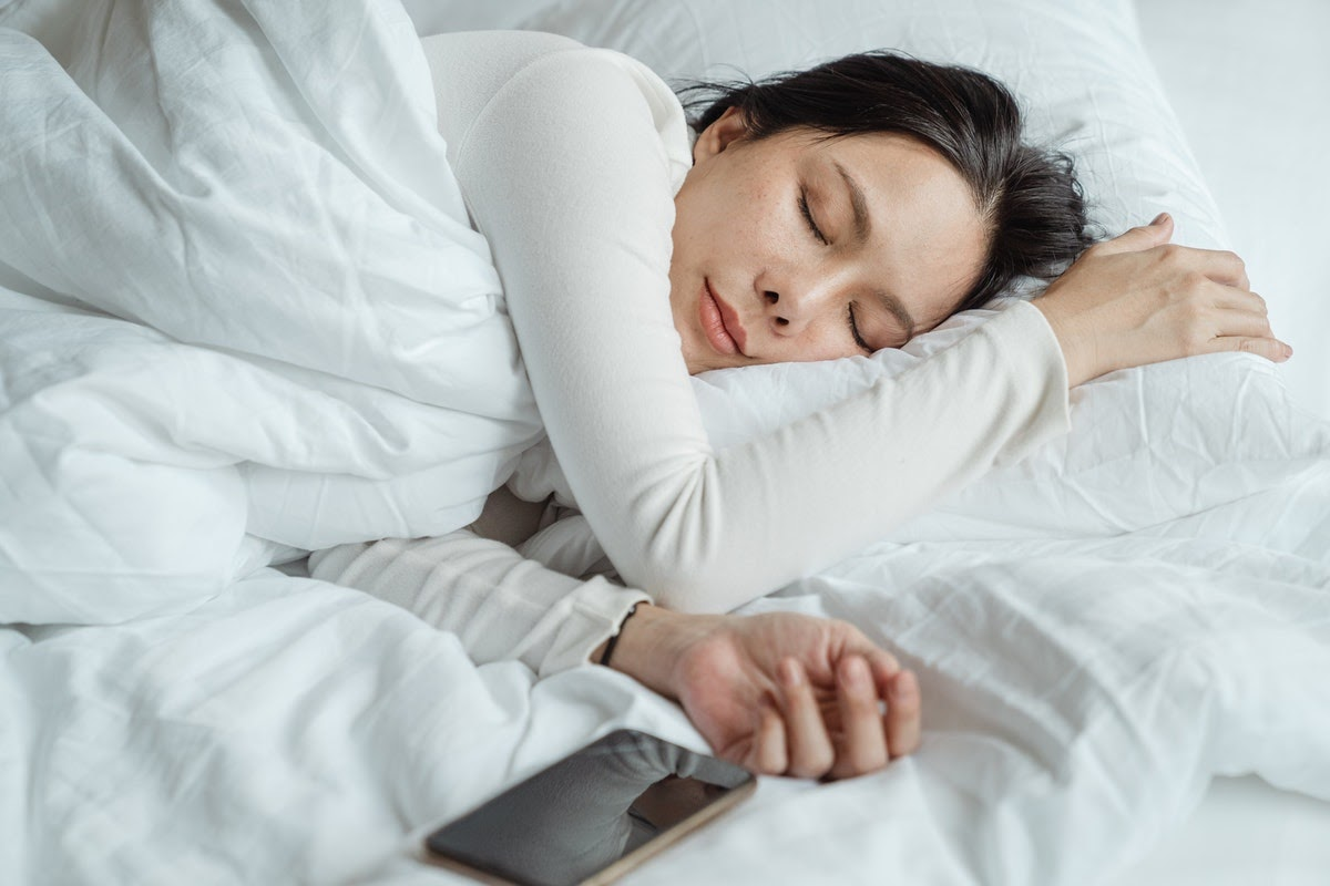 a woman sleeping next to her iPhone