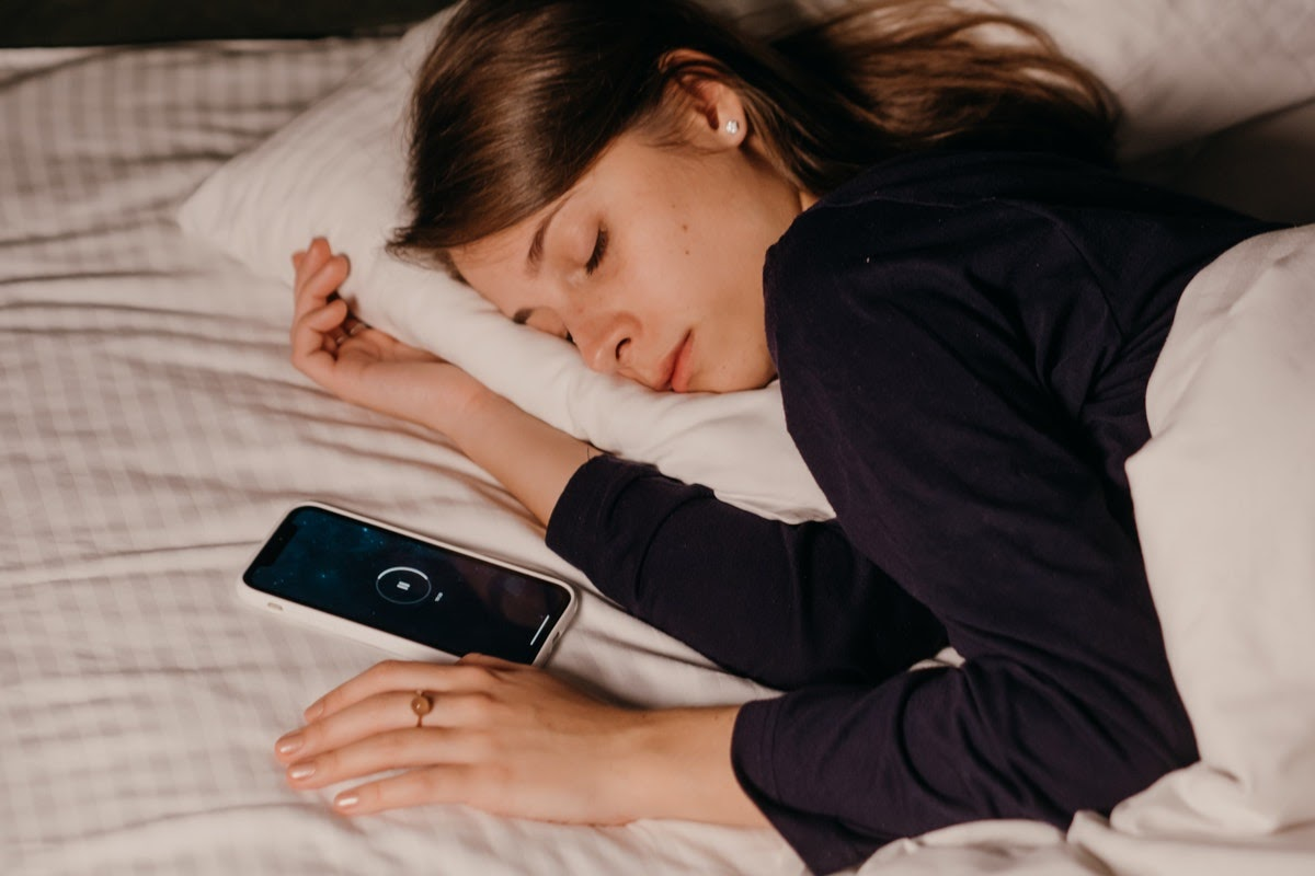 a woman asleep next to her phone playing music