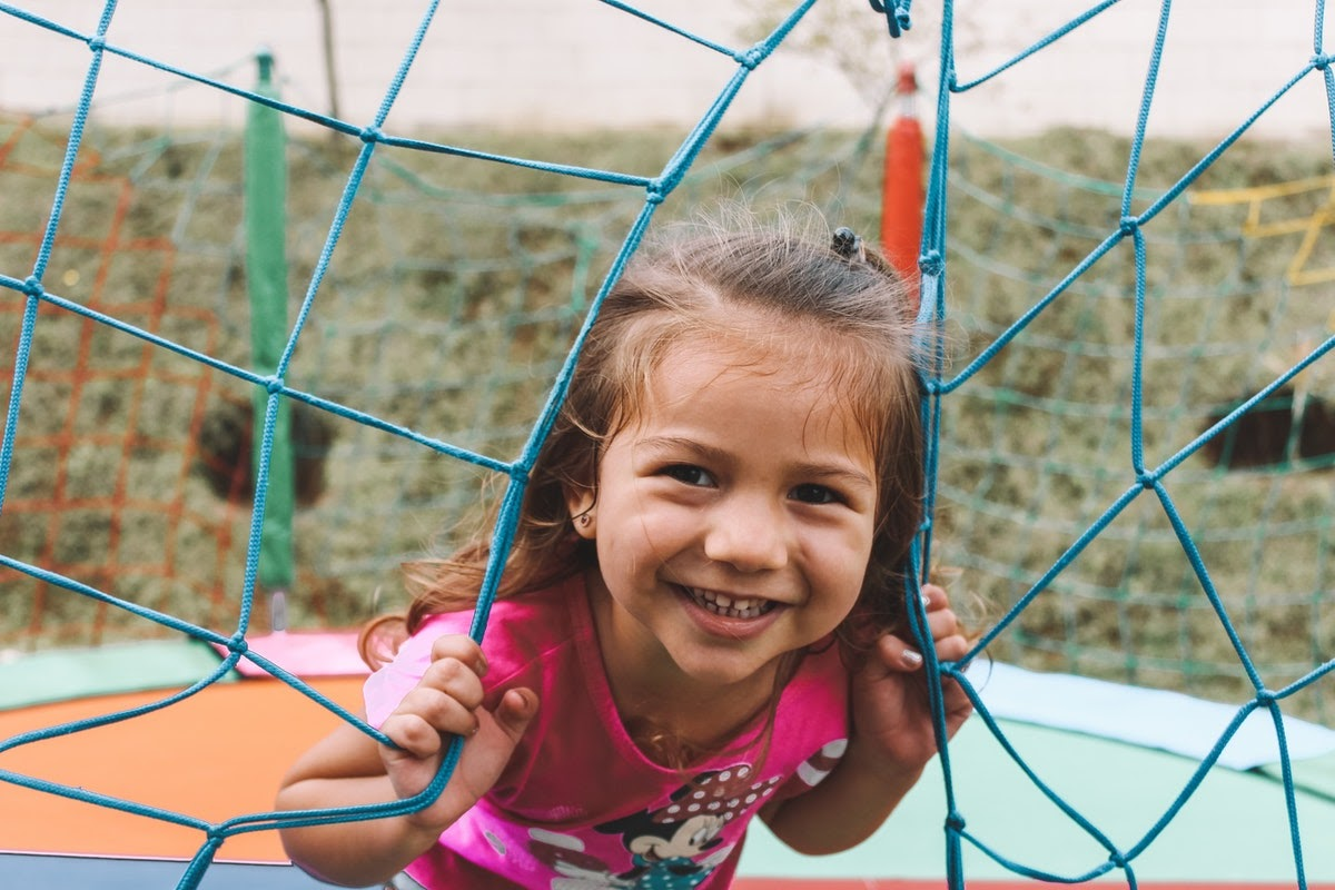 a young girl peeking between an outdoor net