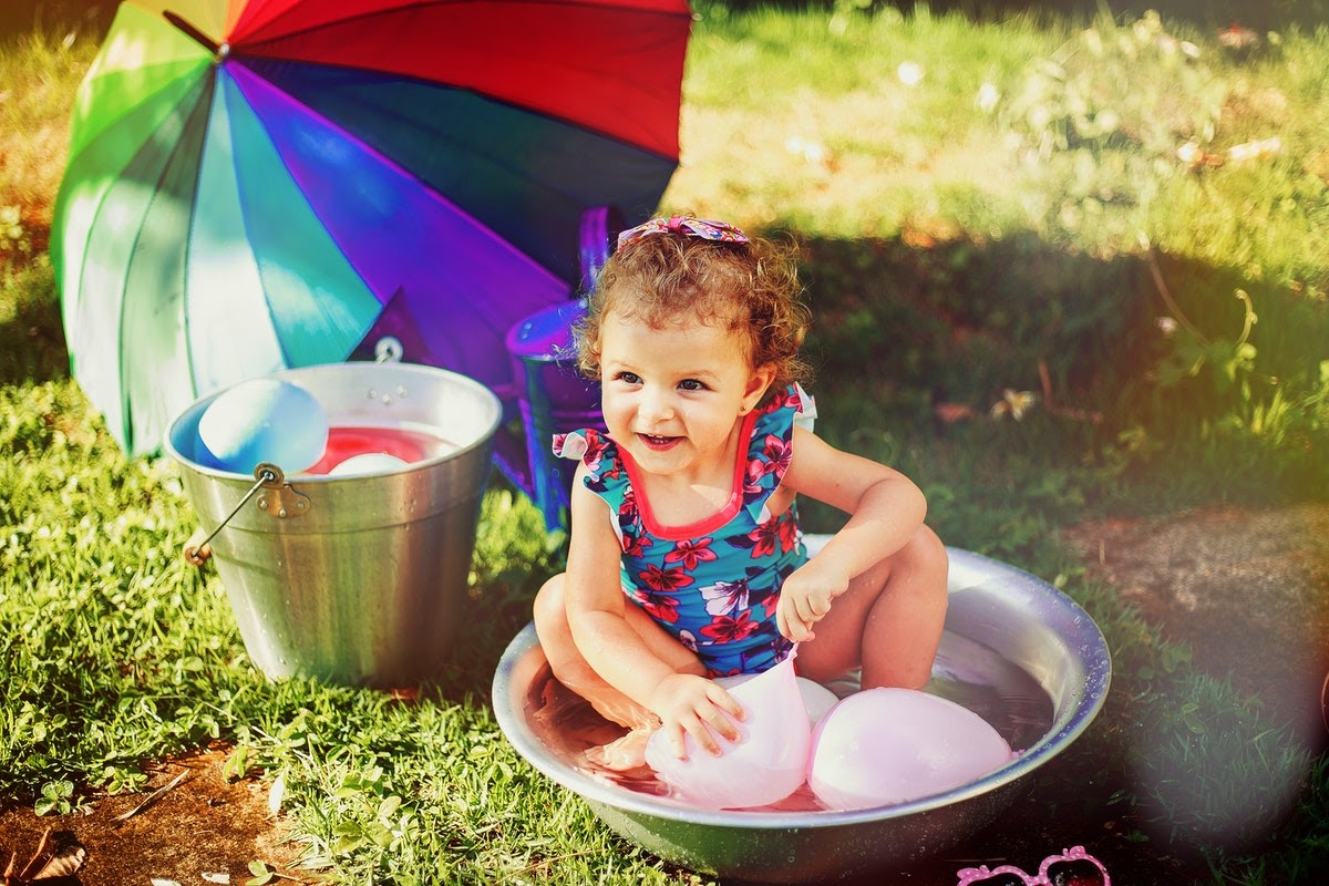 a little girl playing with water balloons