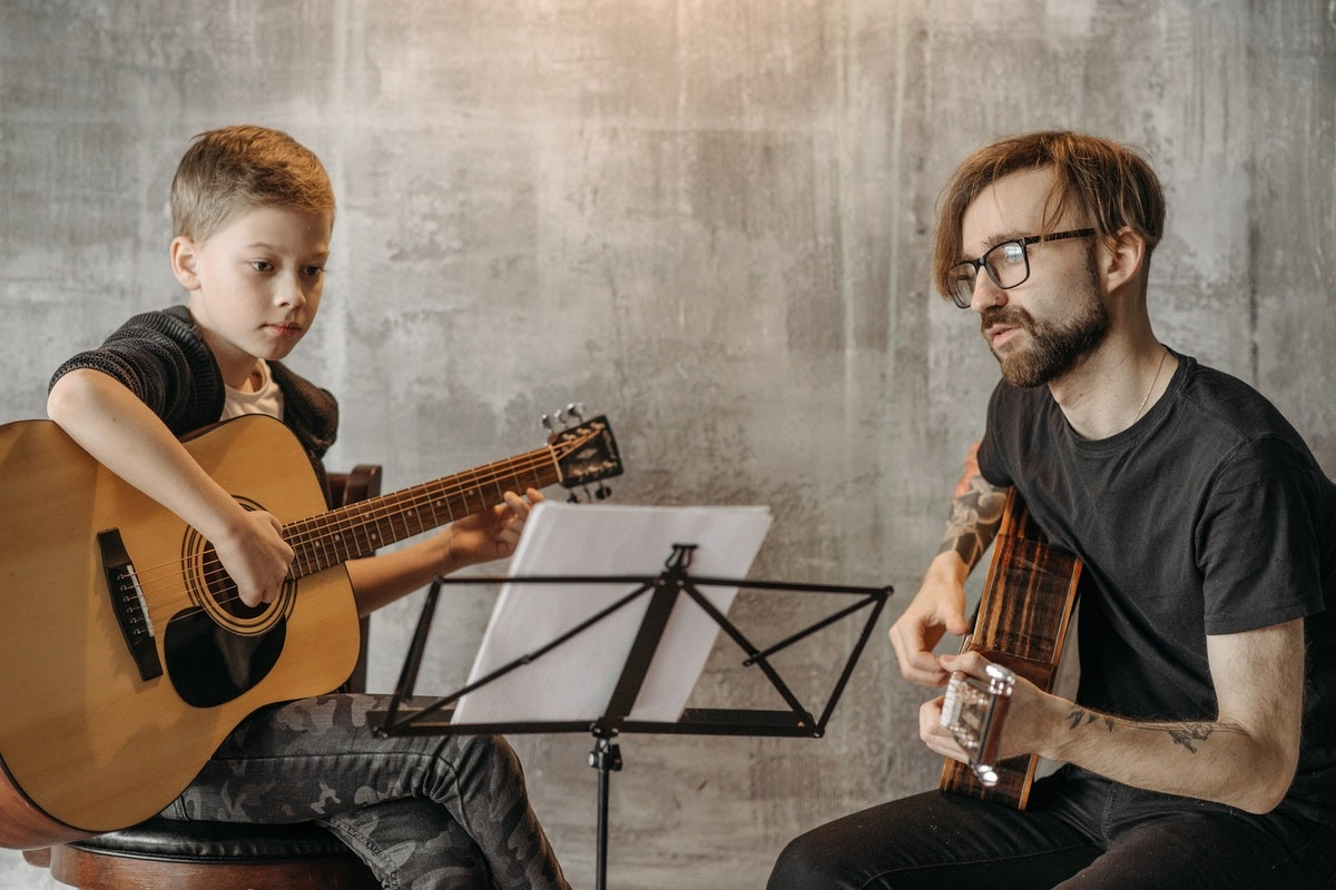 a teacher and a student in a guitar lesson
