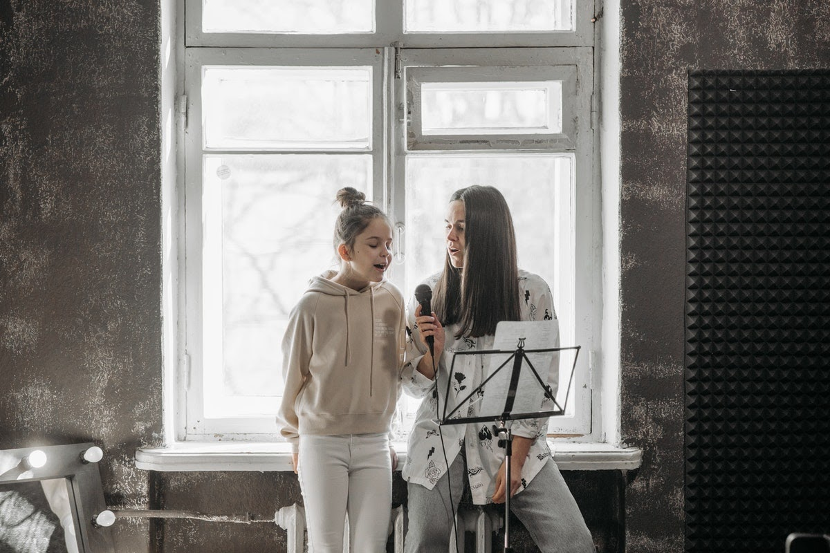 a woman and a young girl in a singing lesson