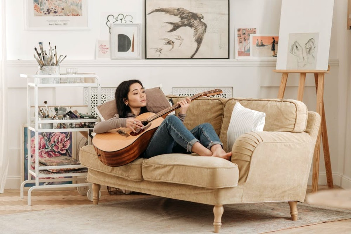 woman playing guitar on a couch