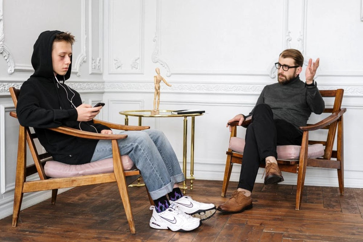 a therapist talking to a teen who is listening to music on his phone