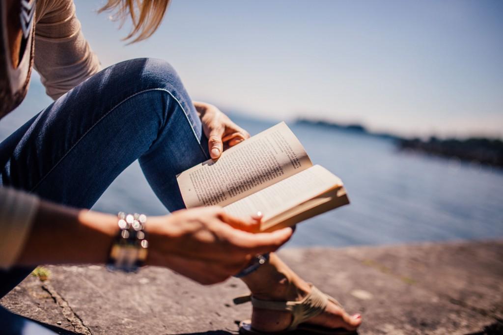 Girl reading book near water