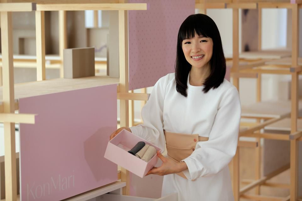 Marie Kondo holds a box standing beside a poster with the word KonMari on it.