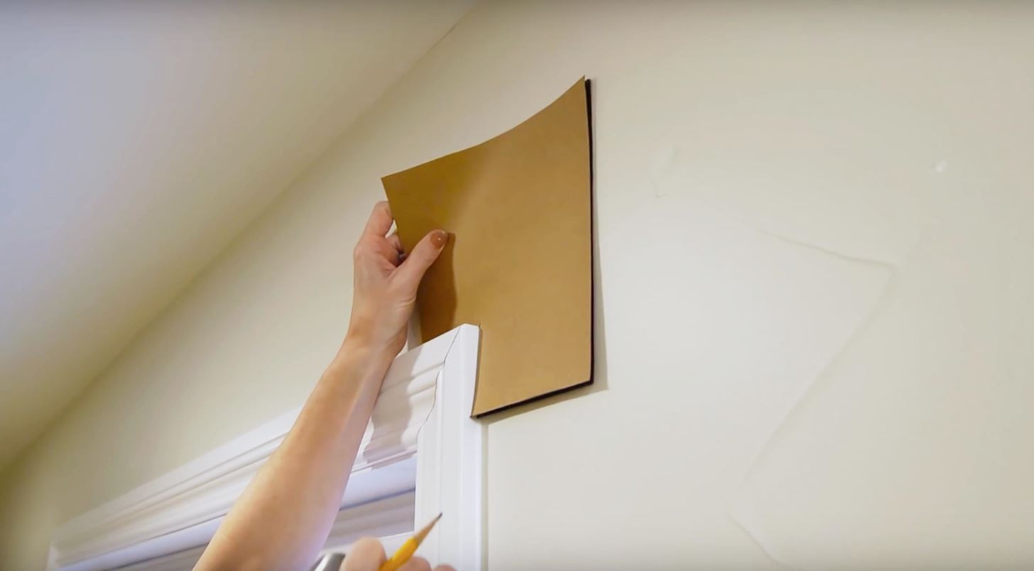 A student holds  piece of cardboard up to the wall to prevent damage while decorating