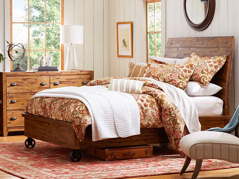 A cozy bedroom with rustic elements like wood, cozy blankets, and floral prints.