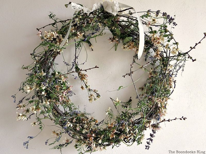 A rustic wreath of dried flowers tied with a lace bow on a white dorm room wall