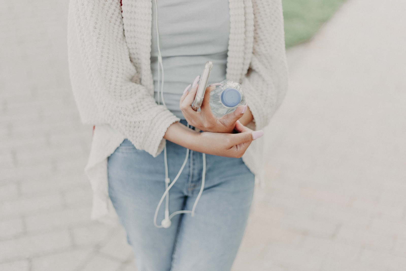 Woman holding water bottle and phone