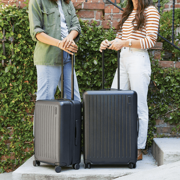 two women holding suitcases
