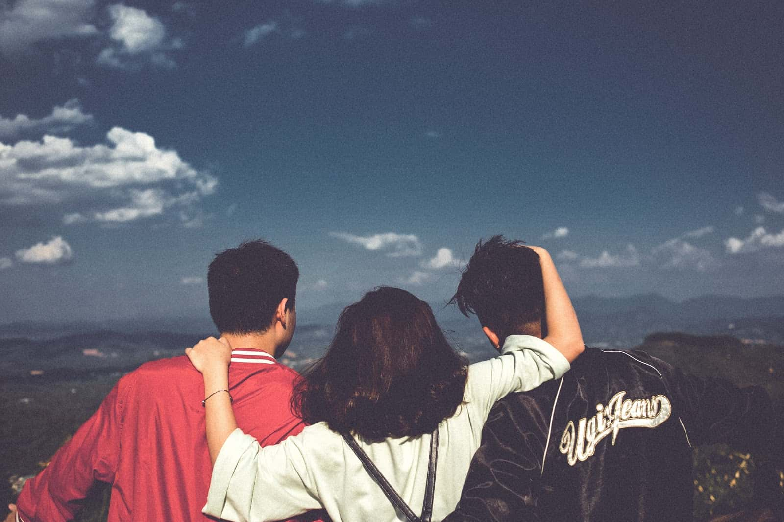 three friends looking at a view of a mountainside