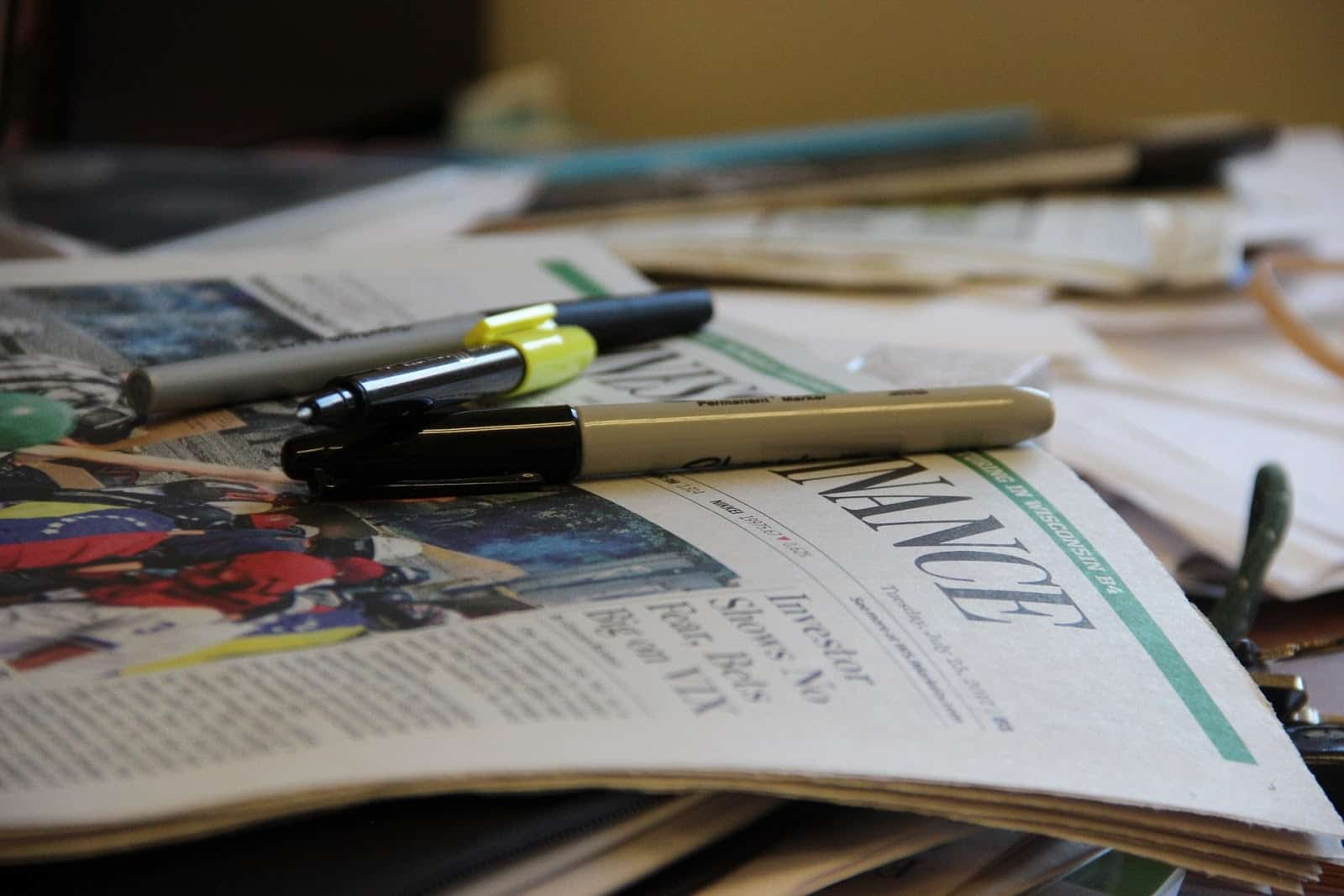 newspaper with pens sitting on top